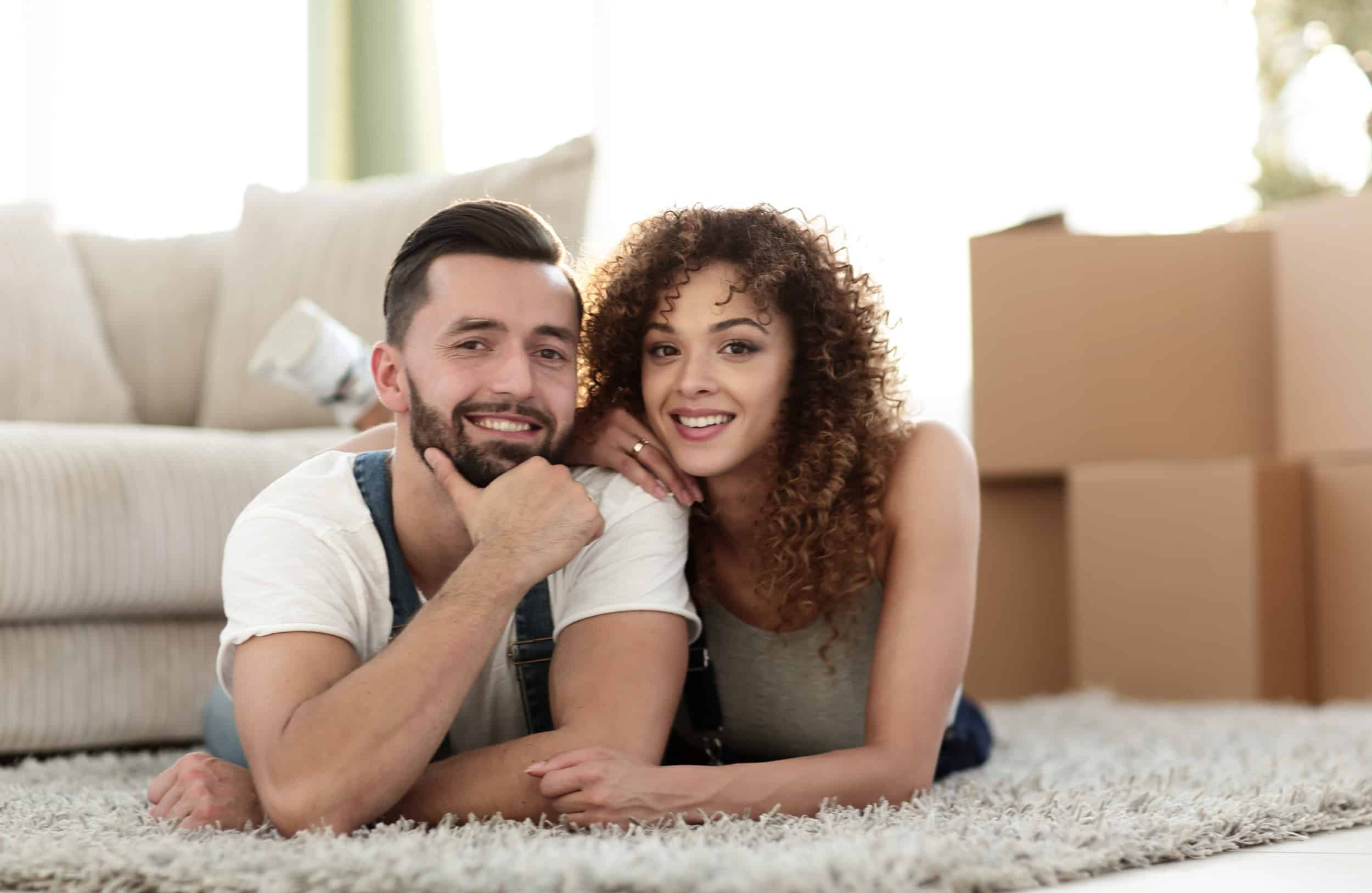 A young couple smiling in a new home surrounded by moving boxes