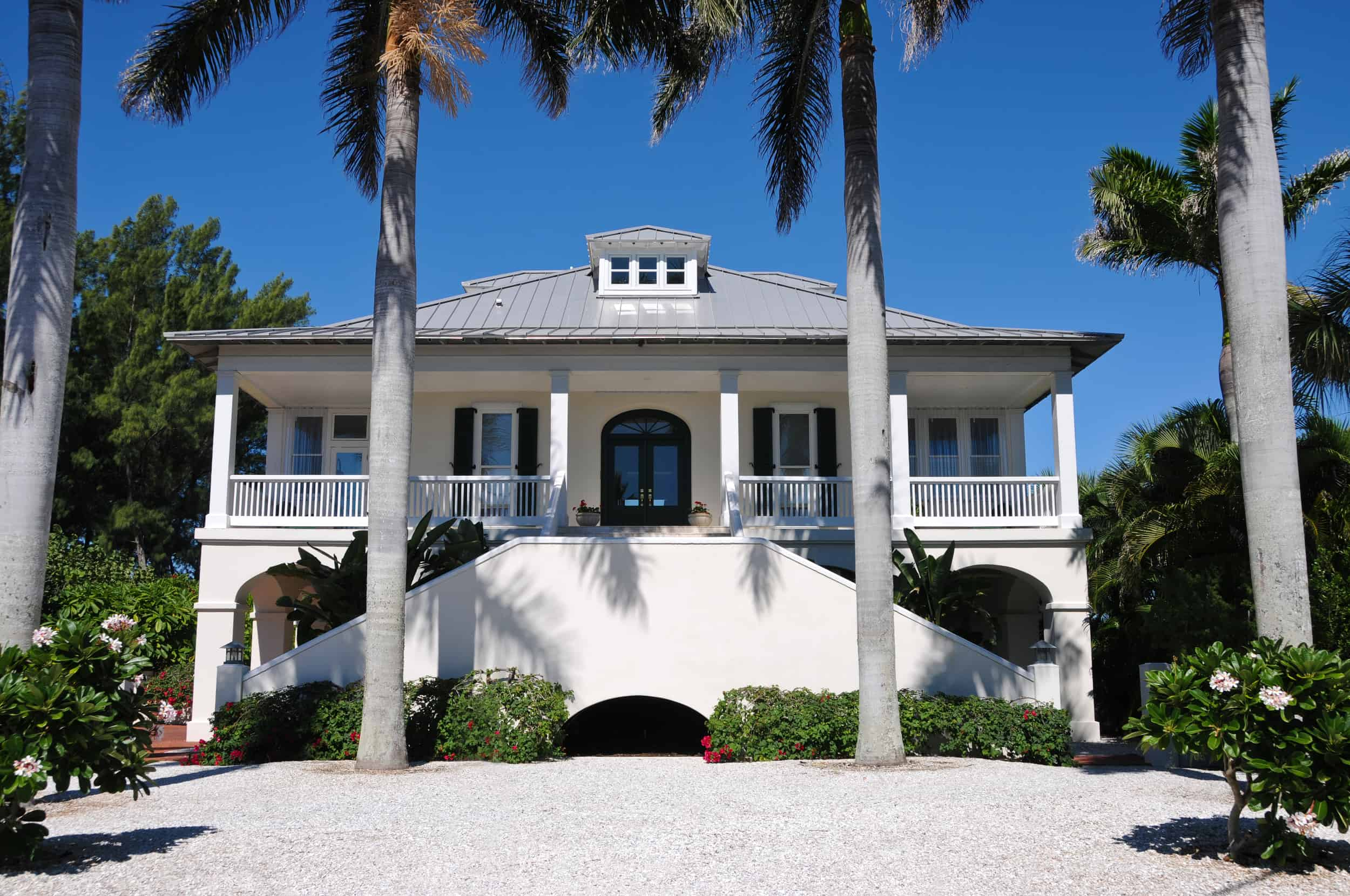 A large white Southern home with columns and palm trees